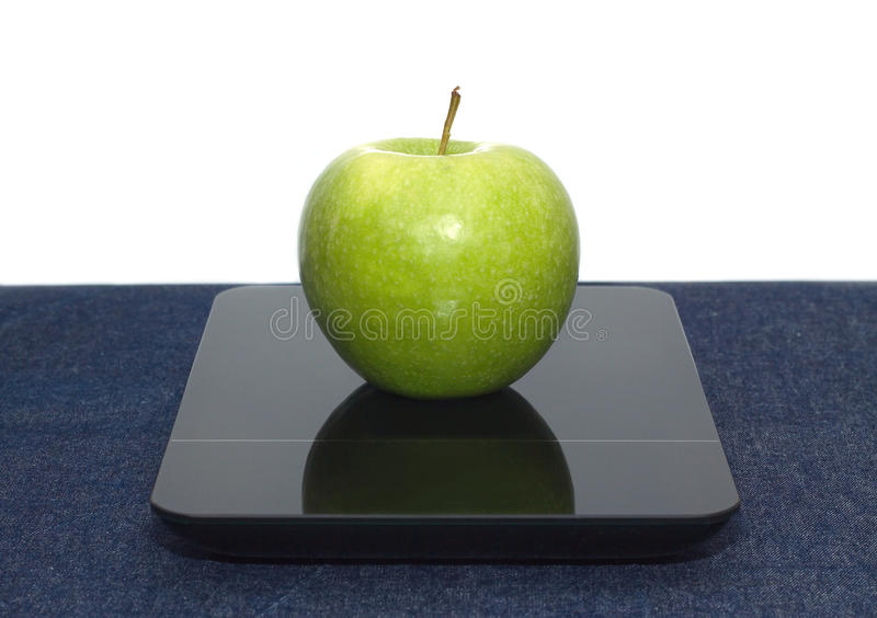 Green apple on kitchen scales closeup. Tasty green apple on kitchen scales on table covered jeans cloth against white background. Front view closeup stock photos