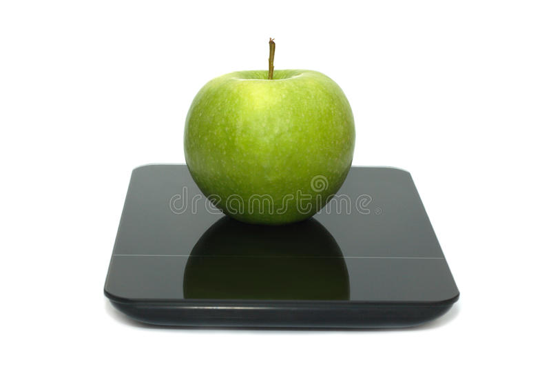 Green apple on kitchen scales isolated closeup. Tasty green apple on kitchen scales isolated on white background. Front view closeup stock photography