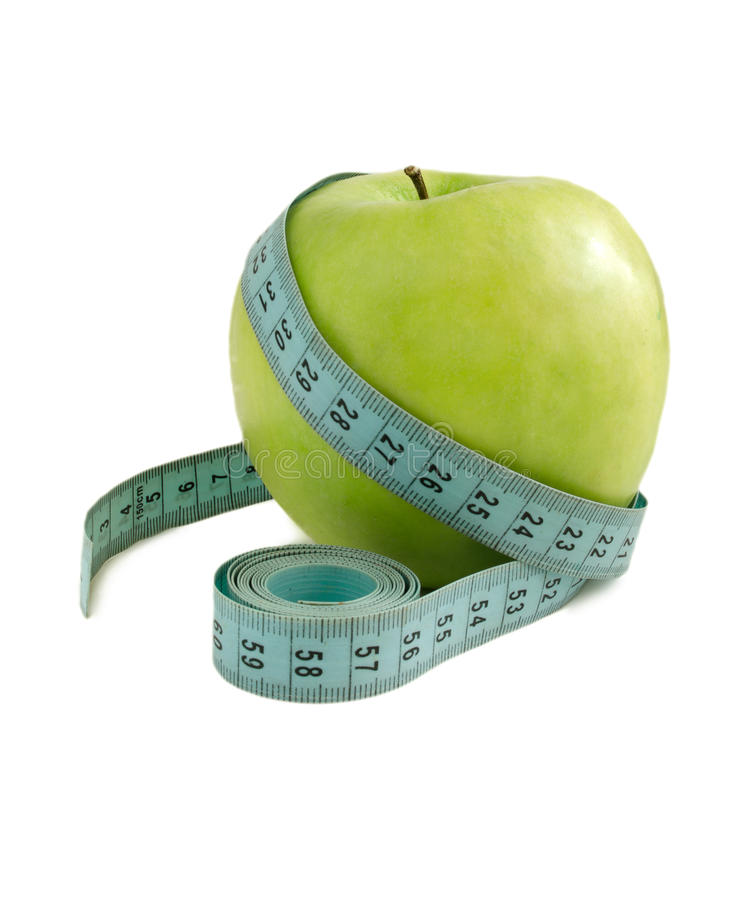 Green apple with a measuring tape on a white background. royalty free stock photography