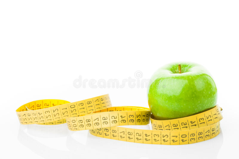 Green apple with measuring tape on white. Dieting concept. Green apple with measuring tape on white background royalty free stock image
