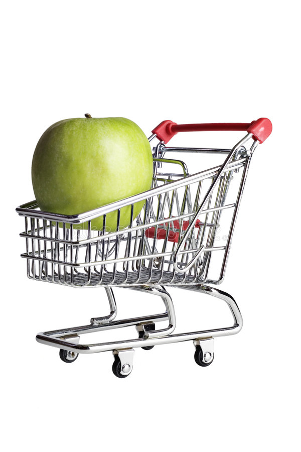 A green apple in a miniature shopping cart. royalty free stock photography