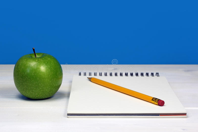 Green Apple And Notebook With Pencil On White Wooden Desk Royalty Free Stock Photos