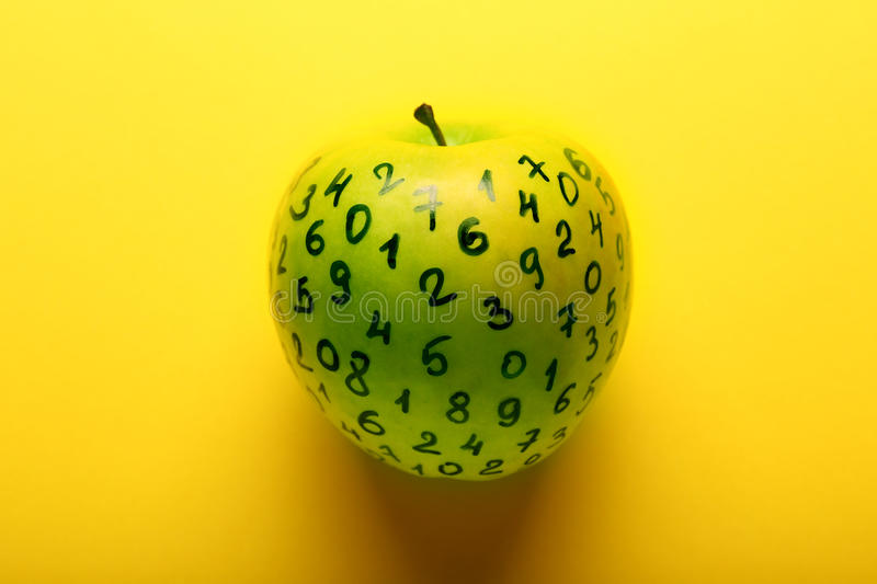 Green apple with numbers on yellow background. Close up royalty free stock image
