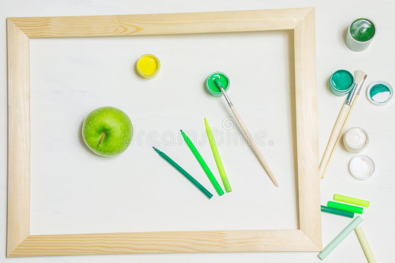 Green apple and paintbrushes in a wooden frame stock photos