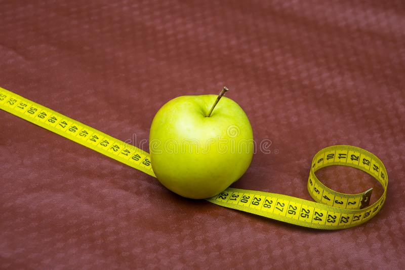 Green apple and ribbon on brown background. Measuring tape and apple. Fruits for weight loss. low calorie product. apple juice stock photos