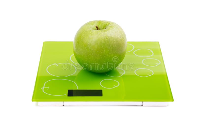 Green apple on scales. Green apple with water drops on scales. Isolated royalty free stock photo