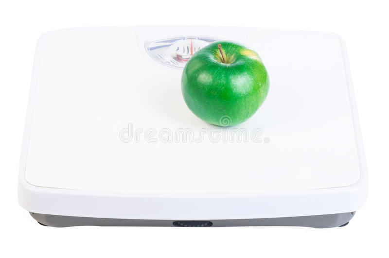 Green apple on the scales. Green apple on the white floor scales isolated on the white background stock photo