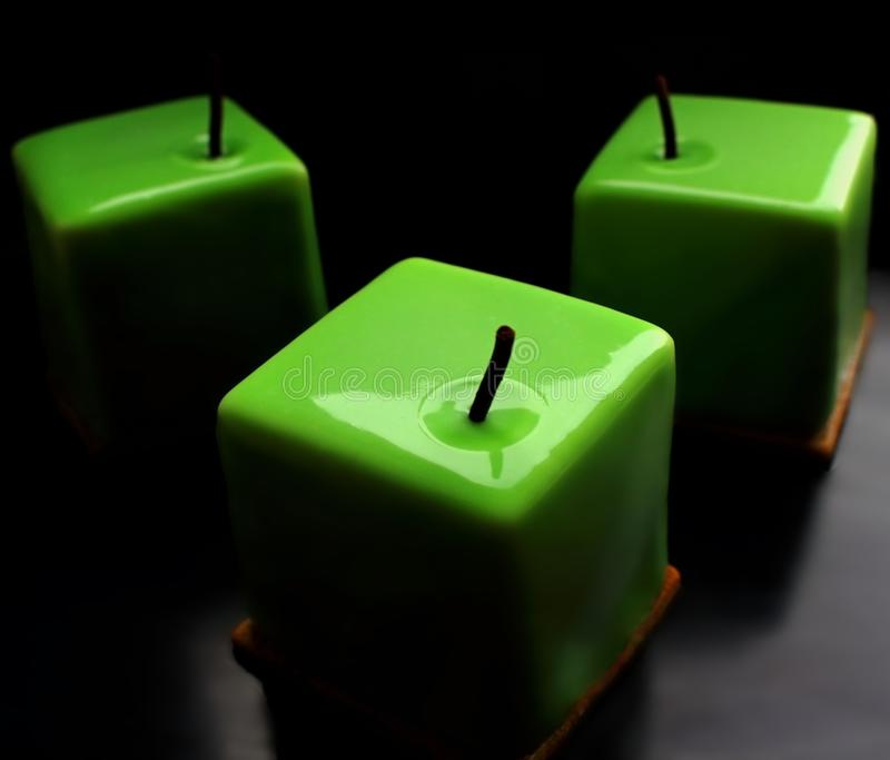 Green apple shiny glazed cube desserts on black background stock photography