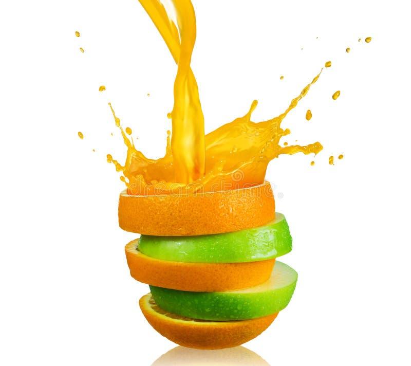 Green apple and splashing orange juice. On white background royalty free stock images