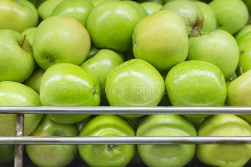 Green apple on the supermarket shelf, displayed for sale stock photo