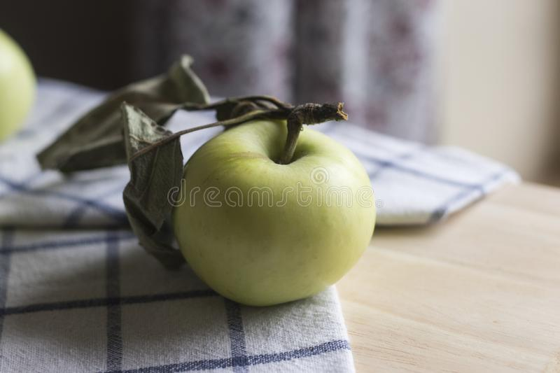 Green apple on the tablecloth. Green apple with leaves on the tablecloth. Summer time royalty free stock photo