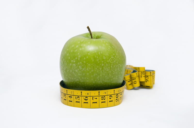 Green apple with tape measure royalty free stock photo