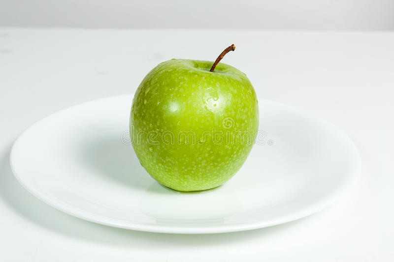 Green Apple with water drops in a plate. Green Apple with water drops in white plate stock photos