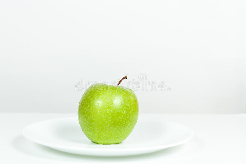 Green Apple with water drops in a plate. Green Apple with water drops in white plate stock image