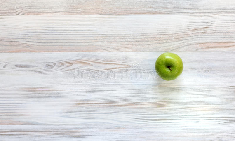 Green apple on wood background. Bright green apple located on well-textured birch kind of wood stock photos