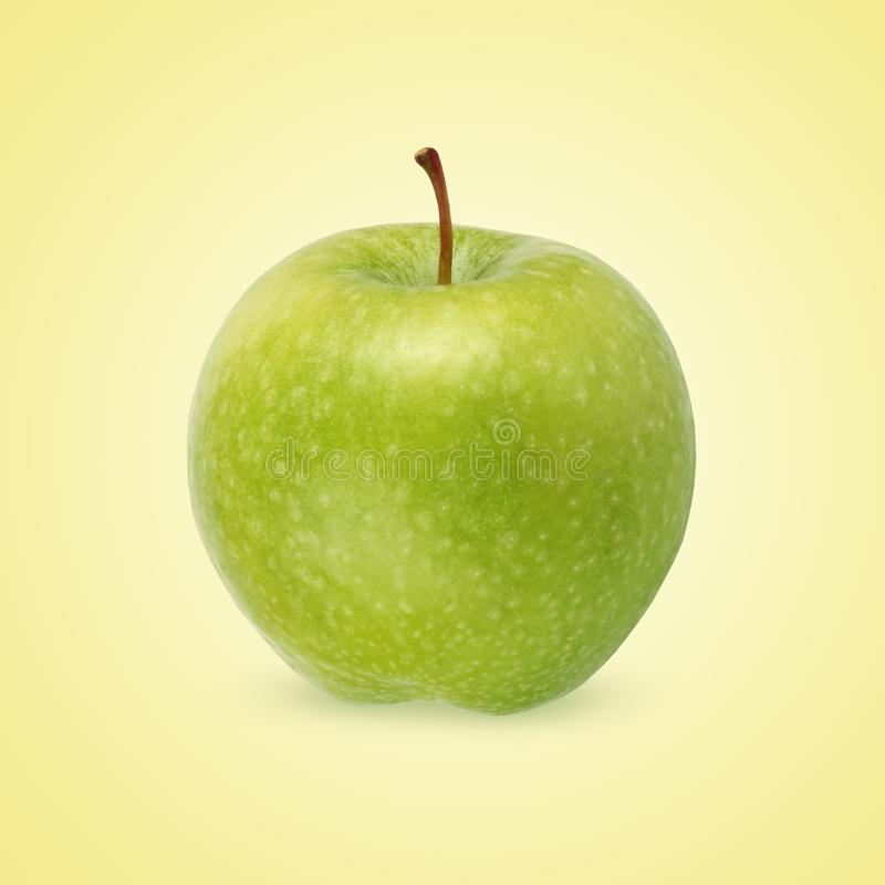 Green apple on a yellow background royalty free stock photos