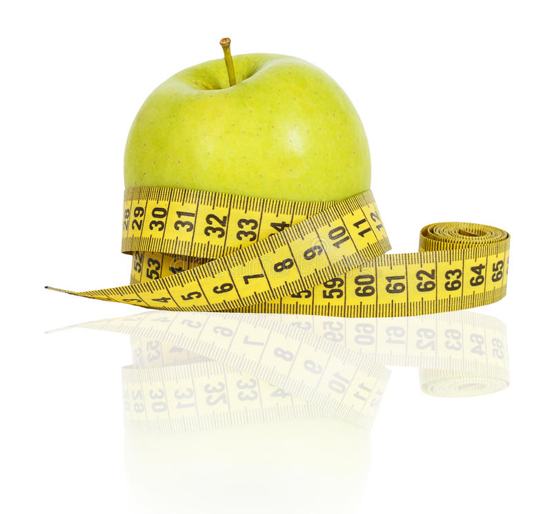 Green apple and yellow measuring tape stock photography