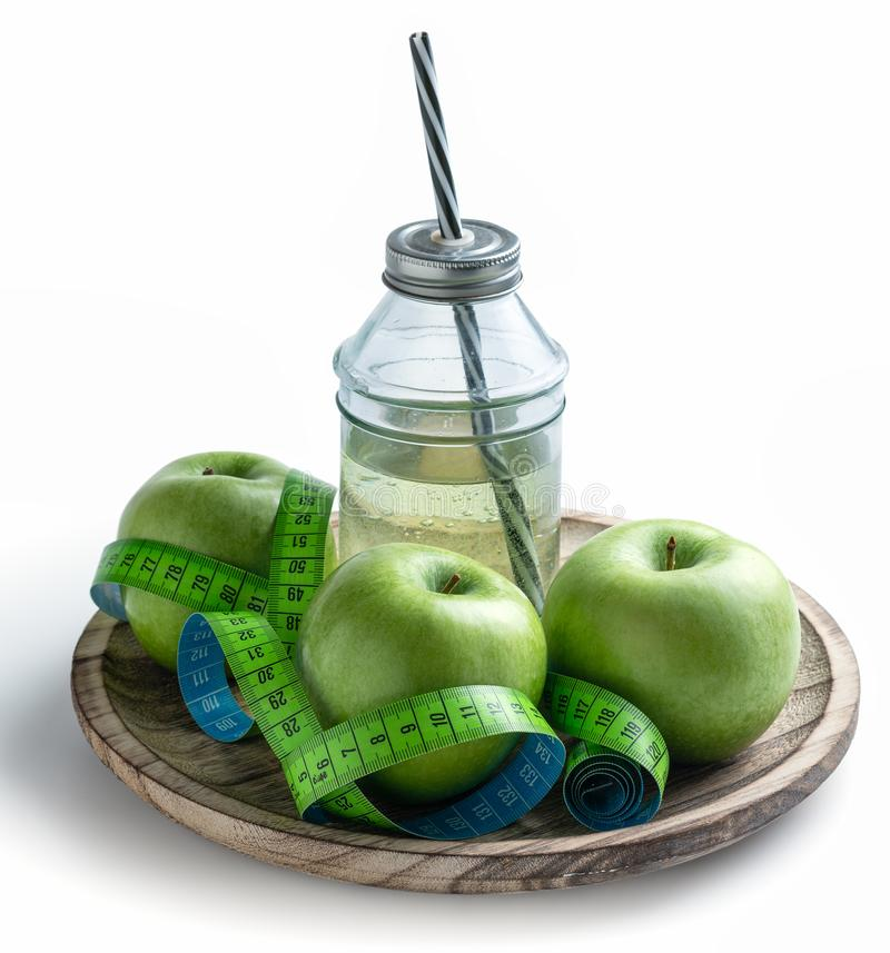 Green apples and apple juice with measuring tape to control weight in the diet. Contains clipping path - image stock photography