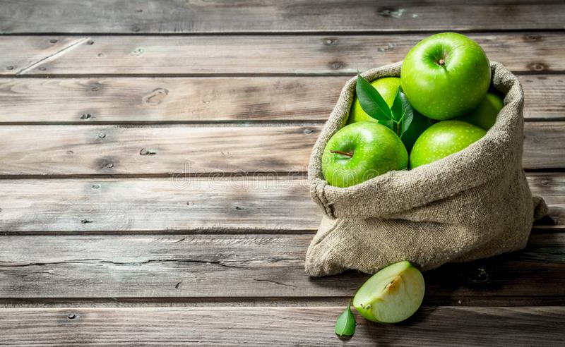 Green apples and Apple slices in an old bag. On grey wooden background royalty free stock photo