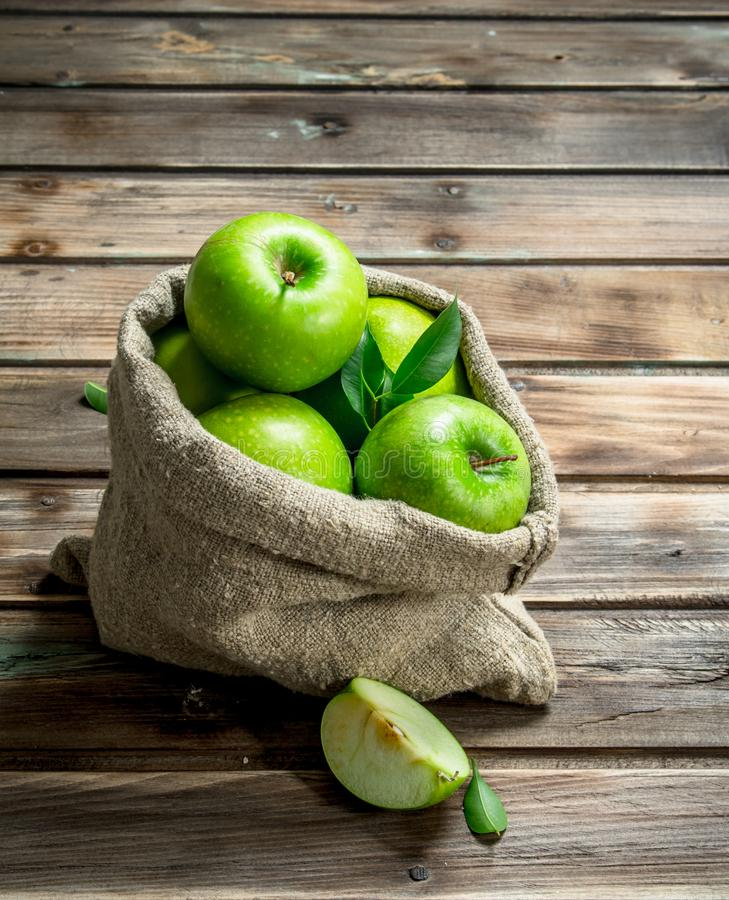 Green apples and Apple slices in an old bag. On grey wooden background royalty free stock images