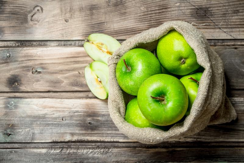 Green apples and Apple slices in an old bag. On grey wooden background royalty free stock photography