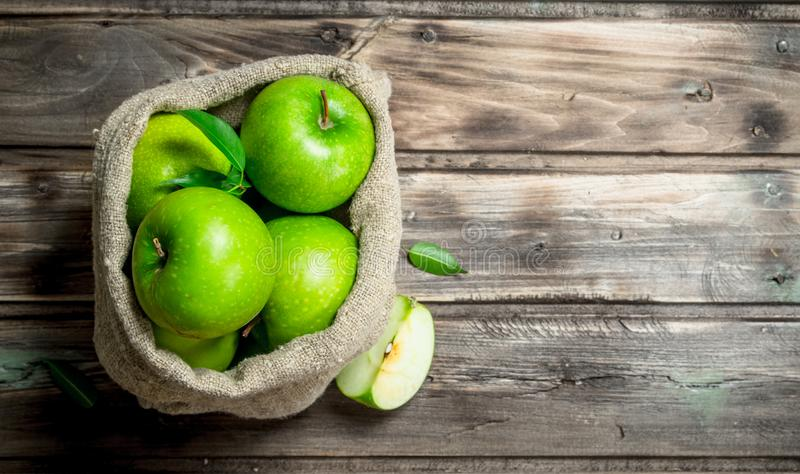 Green apples and Apple slices in an old bag. On grey wooden background royalty free stock image