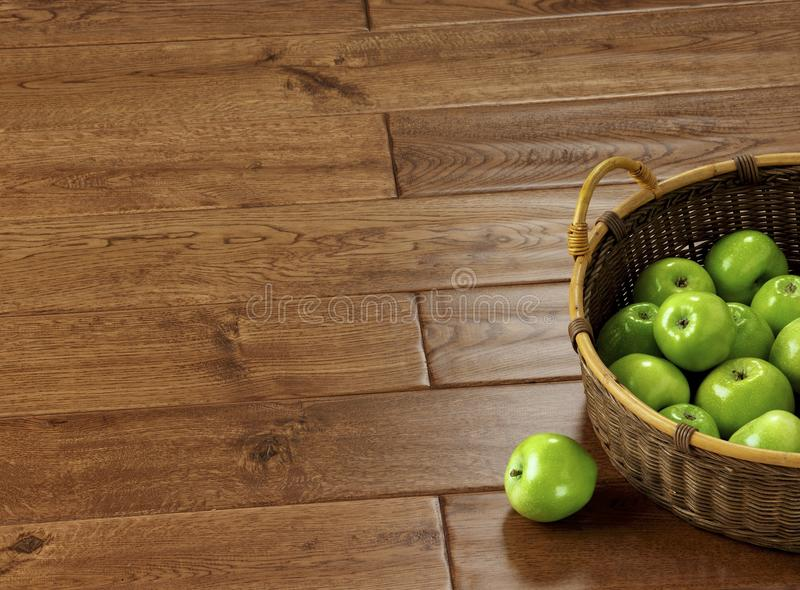 Green apples in a basket on an oak parquet stock images