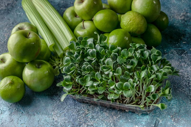 Green apples, celery, limes and milk thistle microgreen on a concrete background. Detox program, diet plan, weight loss royalty free stock photo