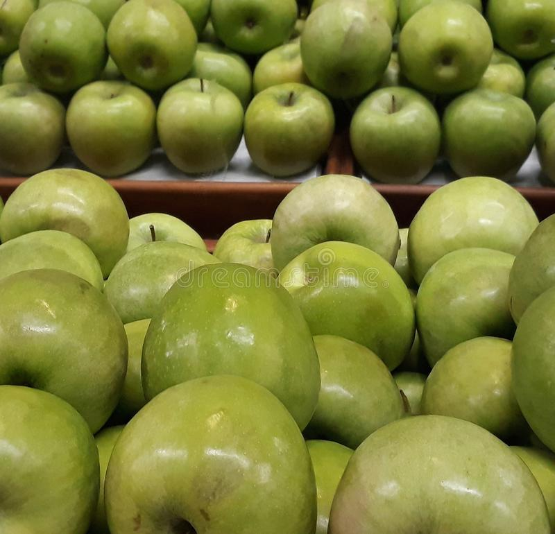 Many succulent green apples. Green apples in a market gondola with mirror many succulent royalty free stock photography