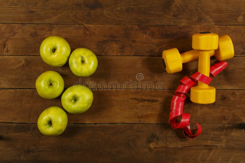 Green apples with a measuring tape and dumbbells on a wooden background. Healthy food. View from above. royalty free stock image