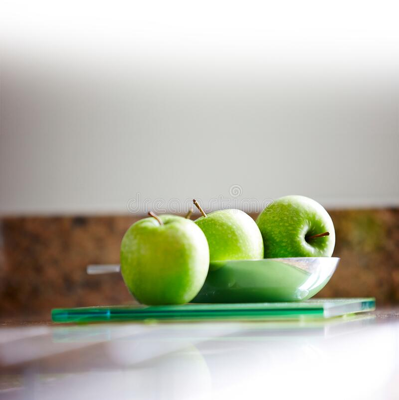 Green apples in a plate. Three green apples in a plate over table royalty free stock photo