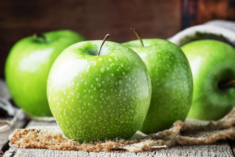 Green apples on vintage wooden background, selective focus stock photos