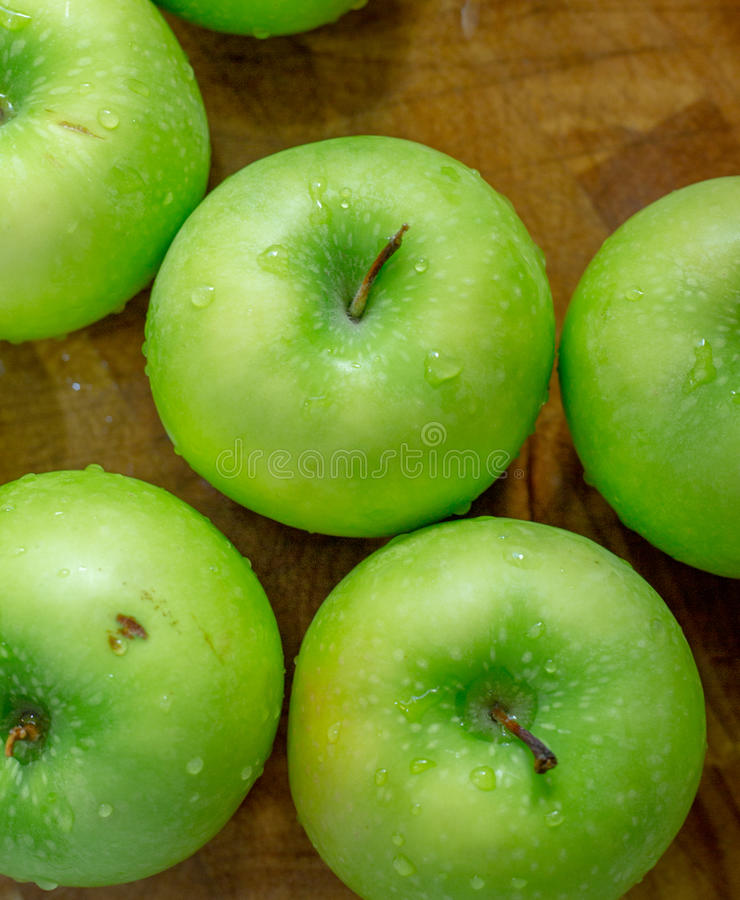 Green Apples. Washed green apples on the chopping block ready to be sliced for apple pie royalty free stock image