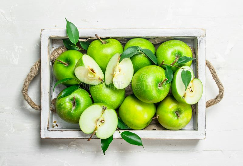 Green apples in a wooden tray. On white rustic background royalty free stock photo