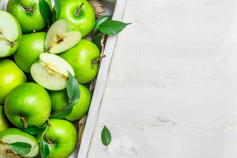 Green apples in a wooden tray. On white rustic background royalty free stock image
