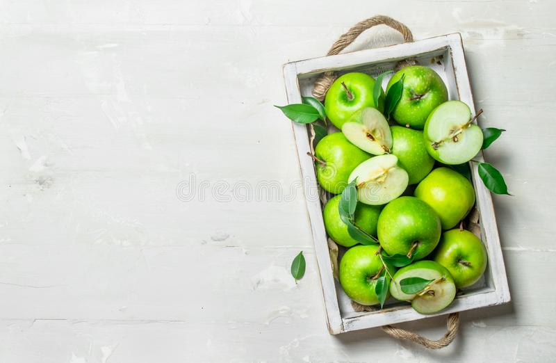 Green apples in a wooden tray. On white rustic background royalty free stock photos