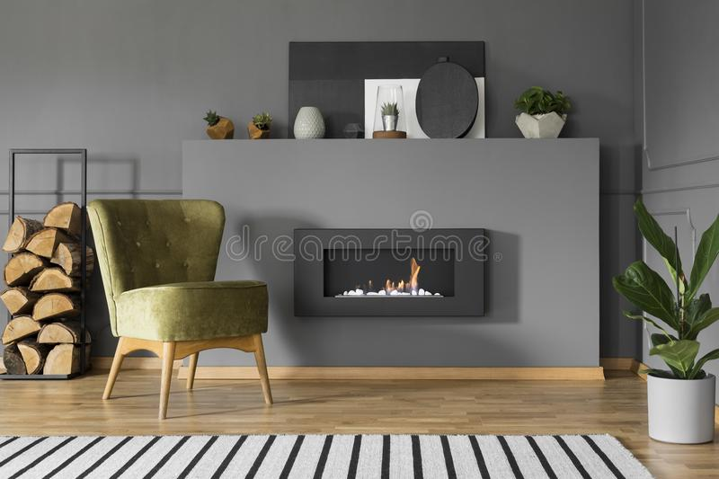Green armchair and firewood next to fireplace in grey living room interior with plant. Real photo royalty free stock images