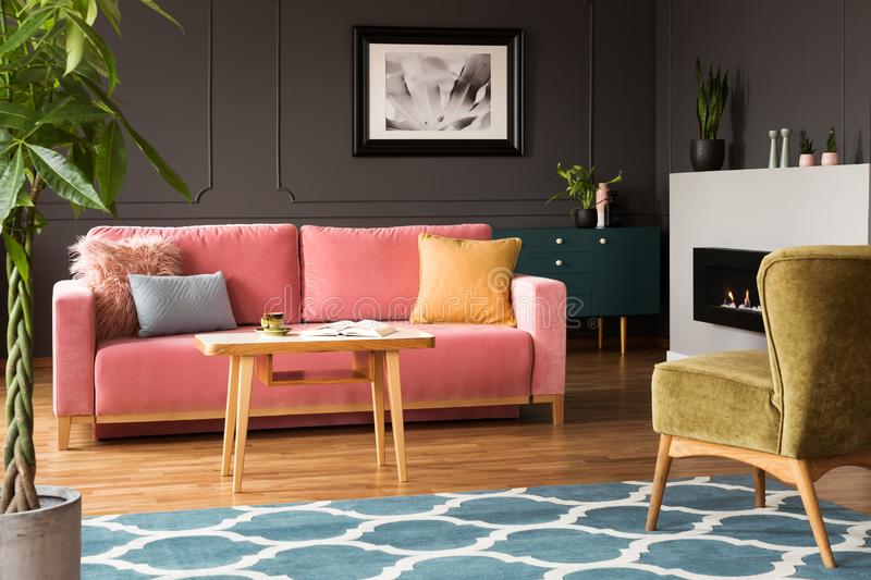 Green armchair and pink sofa in colorful living room interior wi. Th blue carpet and poster. Real photo concept stock image