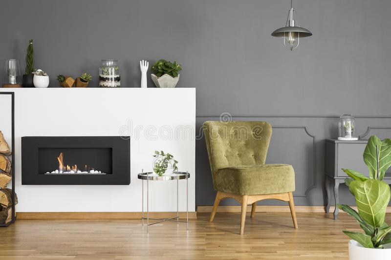 Green armchair and silver table next to fireplace in grey apartment interior with plant. Real photo royalty free stock photo