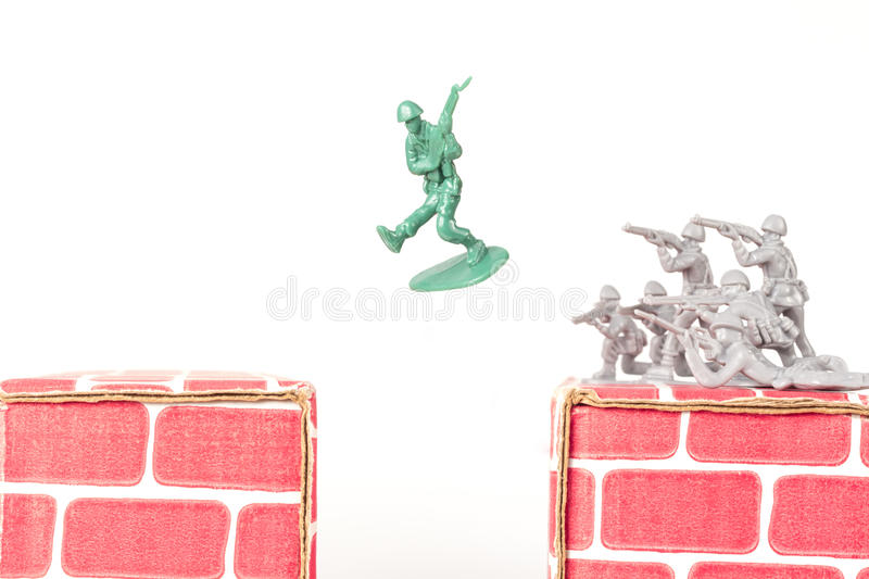 Green Army Man Escapes. Green army man jumps ravine to escape gray army stock image