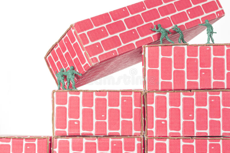 Green Army Men Teamwork. Green army men using teamwork to make progress up the toy brick stairs stock photo