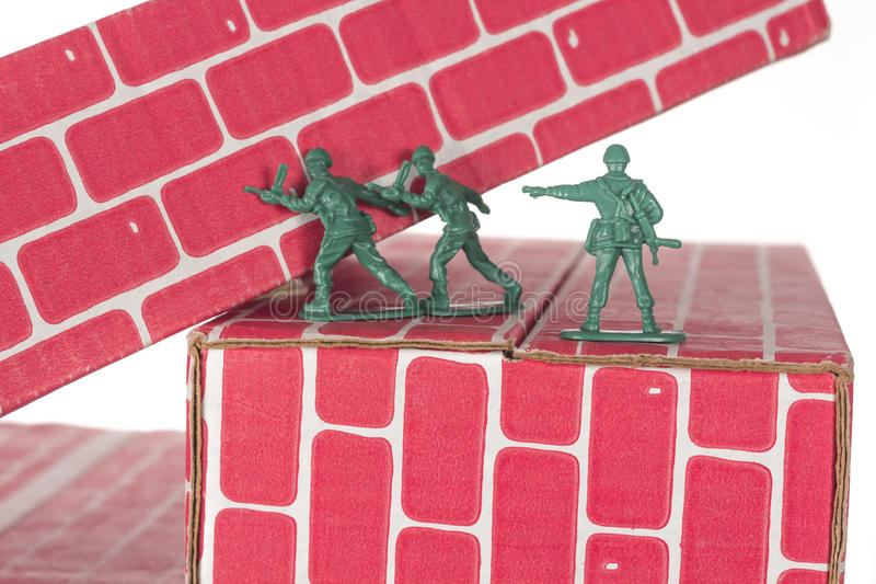 Green Army Men Teamwork. Green army men using teamwork to make progress up the toy brick stairs royalty free stock photography