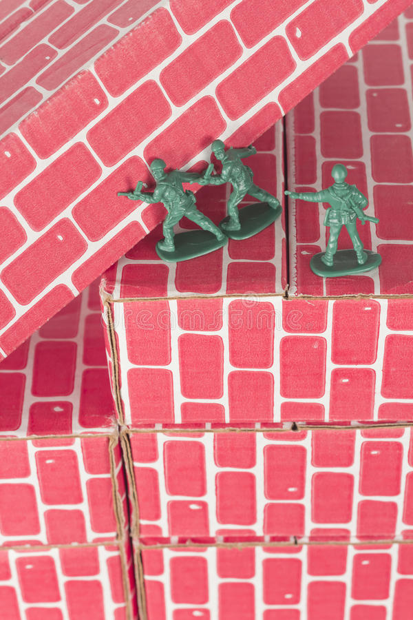 Green Army Men Teamwork. Green army men using teamwork to make progress up the toy brick stairs stock image