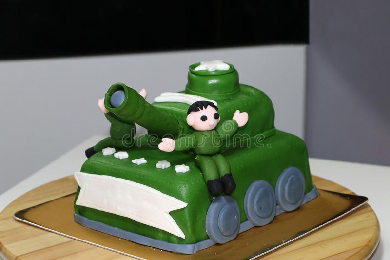 Green army tank cake with edible soldier doll. On it stock photography