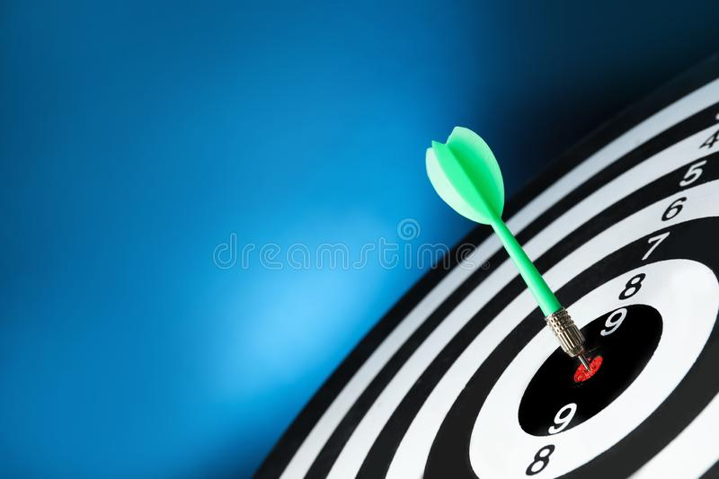 Green arrow hitting target on dart board against blue background. Space for text royalty free stock images