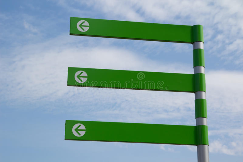 Green Arrow Sign. A Green Empty Directional Arrow Sign with Blue Sky royalty free stock photo