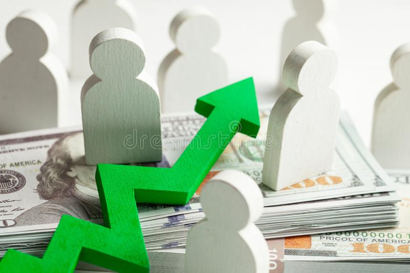 Green arrow up on the background of a bundle of money in cash and staff. Profit growth in business. stock image