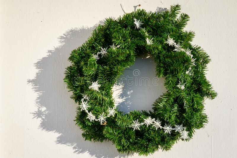 Green artificial holiday wreath with white snowflakes on a white wall, highlighted by late afternoon sunbeam royalty free stock image