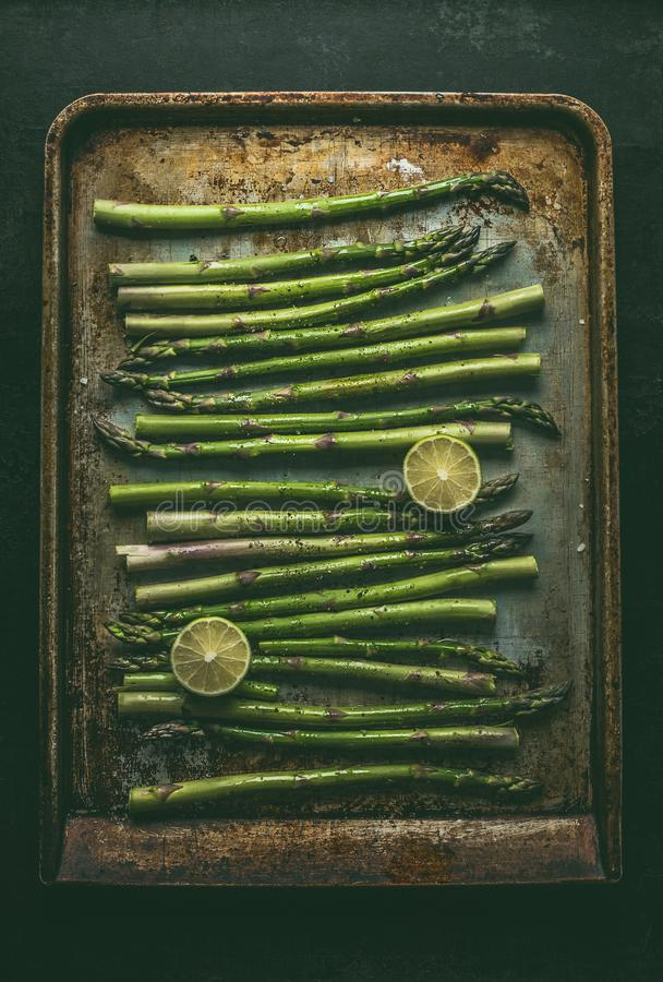 Green asparagus on baking tray on dark rustic kitchen table background, top view.  Healthy vegetarian food  Asparagus cooking prep stock image