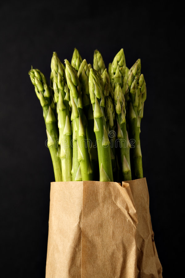 Green asparagus in a brown paper bag stock photos